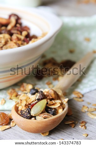Healthy homemade granola or muesli with oats, dried pears, raisin, almonds, hazelnuts and honey in a plate with a spoon and napkin - stock photo