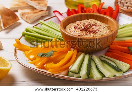 Healthy homemade hummus with assorted fresh vegetables and pita bread. - stock photo