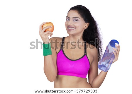 Healthy indian woman holding apple and water while smiling at camera, isolated on white background - stock photo