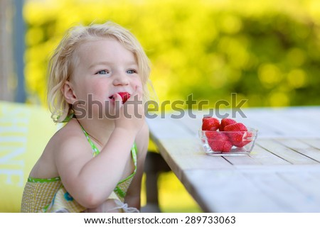 Healthy kid eating strawberries outdoors. Cute little child enjoying fresh berries outdoors. Happy toddler girl having picnic on sunny summer day. - stock photo