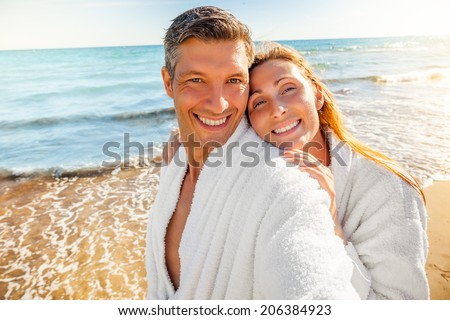 healthy laughing people on tropical wellness spa hotel in bathrobe - stock photo