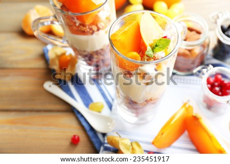 Healthy layered dessert with muesli and fruits on table - stock photo