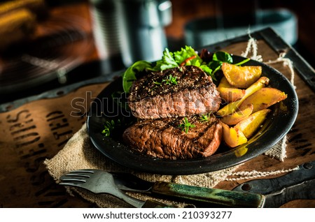 Healthy lean grilled medium-rare beef steak and vegetables with roasted pumpkin and a leafy green herb salad in a rustic pub or tavern - stock photo