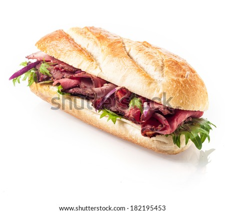 Healthy lean roast beef with leaves of fresh rocket on a freshly baked crusty roll or baguette viewed at an angle on a white background - stock photo