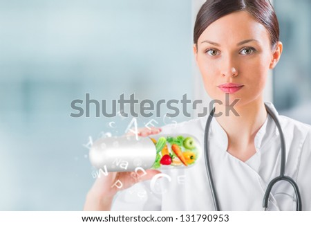 Healthy life concept. Female medical doctor holding vitamins - stock photo