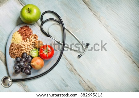 Healthy lifestyle and healthcare concept with food, heart and stethoscope - stock photo