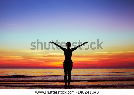 healthy lifestyle background, silhouette of woman with raised hands on the beach at sunset - stock photo