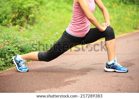 healthy lifestyle beautiful asian woman stretching legs before running   - stock photo