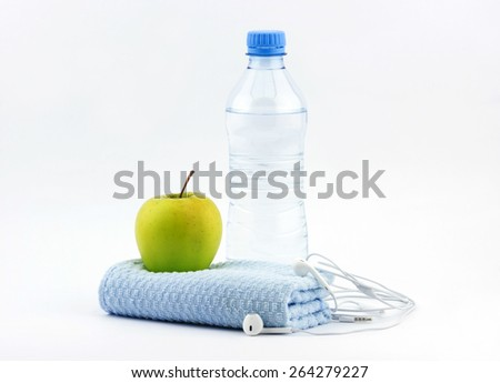 Healthy lifestyle concept. Bottle of water with green apple, fitness towel and headphones on white background - stock photo