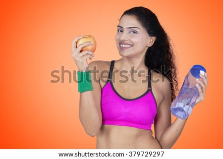Healthy lifestyle concept of Indian fitness model holding apple and bottle of water - stock photo
