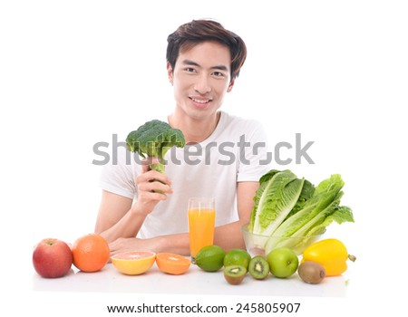 Healthy lifestyle concept - Sportive young man presenting fruits and vegetables - stock photo