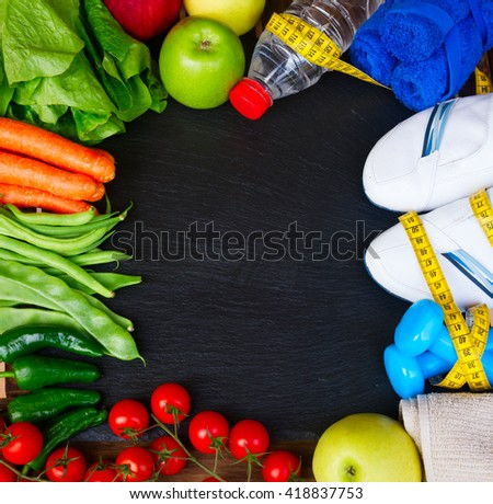healthy lifestyle concept - training shoes, vegetables  and  water frame on black table with copy space - stock photo