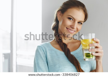 Healthy Lifestyle, Food. Happy Woman Drinking Summer Refreshing Fruit Flavored Infused Water With Fresh Organic Lemon, Lime, Mint. Detox Vitamin-fortified Water. Healthy Eating. Diet Concept.  - stock photo