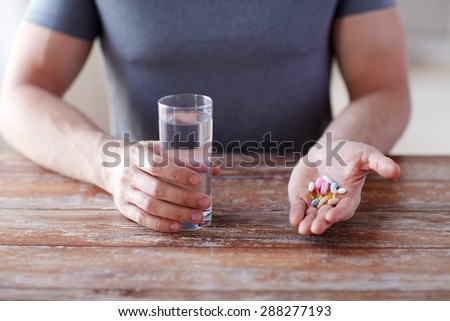 healthy lifestyle, medicine, nutritional supplements and people concept - close up of male hands holding pills with cod liver oil capsules and water glass - stock photo