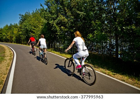 Healthy lifestyle - people riding bicycles in city park  - stock photo