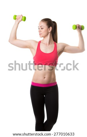 Healthy lifestyle: portrait of young sporty girl doing biceps training, holding dumbbells in flexed arms, studio shot, white background, isolated - stock photo