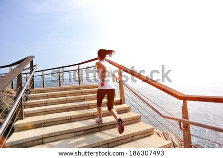 healthy lifestyle sports woman running on stone stairs seaside - stock photo