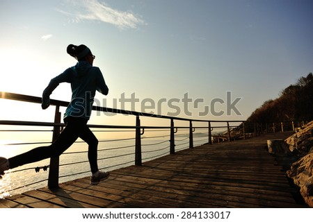 healthy lifestyle sports woman running on wooden boardwalk seaside - stock photo