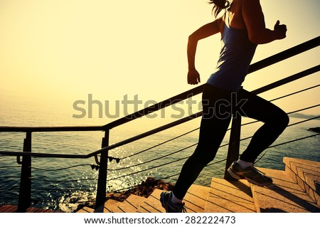 healthy lifestyle sports woman running up on stone stairs sunrise seaside - stock photo