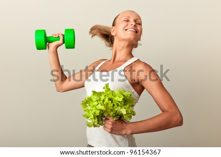 Healthy lifestyle - tanned woman lifting dumbbell and growing green salad - stock photo