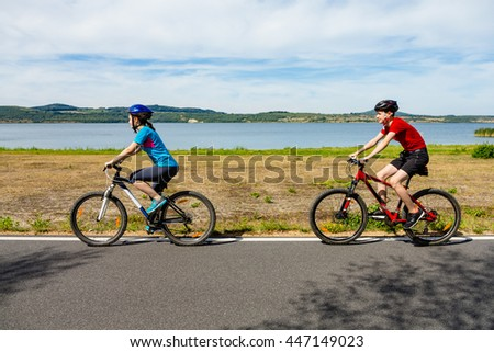 Healthy lifestyle - teenage girl and boy cycling  - stock photo
