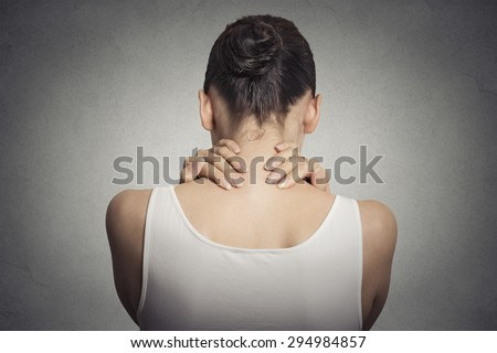 Healthy lifestyle working conditions. Back and spine disease. Closeup back view tired female massaging her painful neck isolated on gray wall background  - stock photo