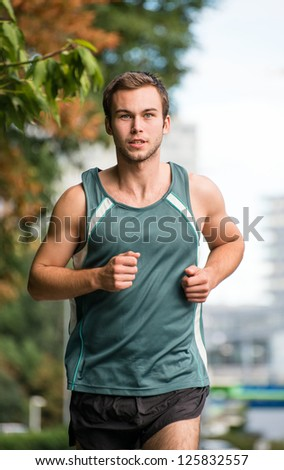 Healthy lifestyle - young attractive man jogging in park - stock photo