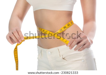 healthy lifestyles concept Woman measuring toned waist. Cropped image of woman in white bra measuring her waist while standing isolated on white with clipping path - stock photo