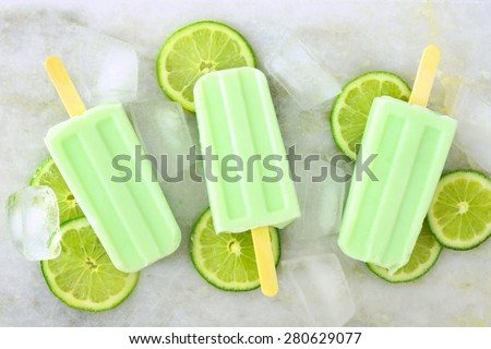 Healthy lime yogurt popsicles with fresh lime slices scattered on a white marble background - stock photo