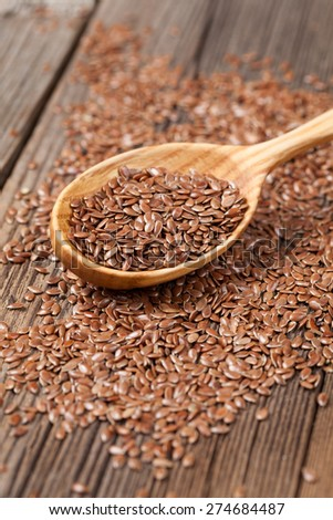 Healthy little brown flax seeds super foods  in wooden spoon. Organic vegetarian nutrition close up. - stock photo