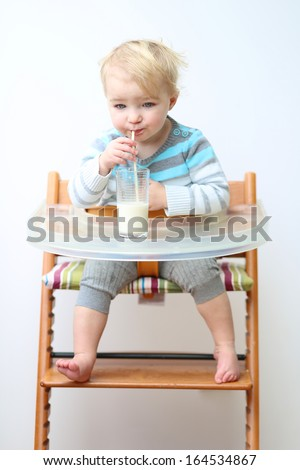 Healthy little toddler girl in blue stripes sweater drinking milk from the glass with straw sitting indoors in high feeding chair against white wall - stock photo