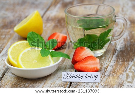 Healthy living card with glass of mint tea, lemon and strawberries  - stock photo