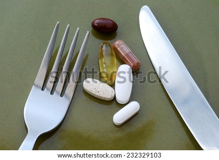 Healthy living concept showing vitamin pills on dinner plate - stock photo
