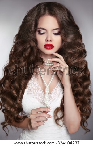 Healthy long hair. Beauty Portrait of a beautiful fashion girl with sensual red lips. Wedding make up and waving hairstyle. Luxury bride modern style.  - stock photo