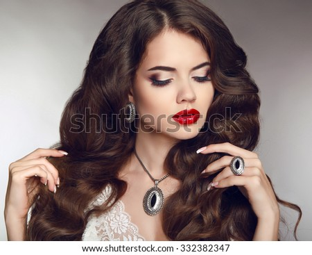 Healthy long hair. Makeup. Jewellery and bijouterie. Beautiful brunette girl model with luxury fashion earrings jewelry.  - stock photo