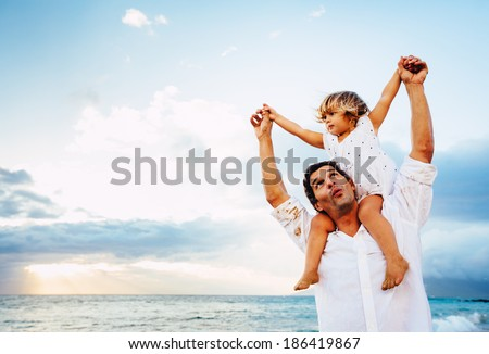 Healthy loving father and daughter playing together at the beach at sunset Happy fun smiling lifestyle - stock photo