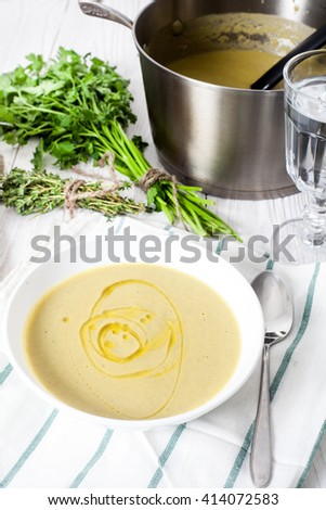 Healthy, low-cal, diet vegetable potato and leek soup based  served in white bowl with olive oil. White wood background. Steel pot with soup, parsley, peppermill and glass of water on back - stock photo