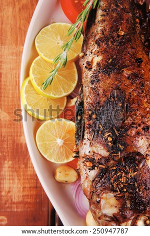 healthy lunch : whole fried sea sunfish on wooden table with lemons peppers and tomatoes and rosemary twig - stock photo