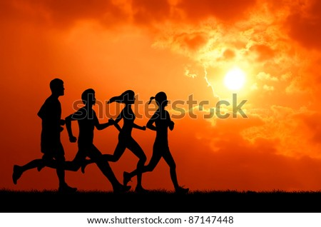 healthy man and woman group running at sunset silhouetted - stock photo