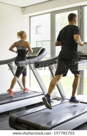 Healthy man and woman running on a treadmill in a gym  - stock photo