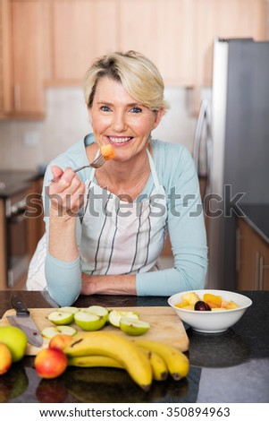 healthy mature woman eating fruit salad at home - stock photo