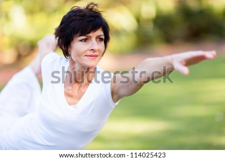 healthy middle aged woman doing fitness stretching outdoors - stock photo
