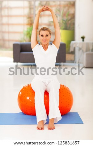 healthy middle aged woman sitting on exercise ball - stock photo