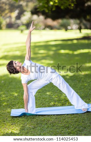 healthy middle aged woman stretching outdoors - stock photo