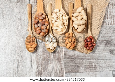 Healthy mix nuts on wooden background. Almonds, hazelnuts, cashews, peanuts - stock photo