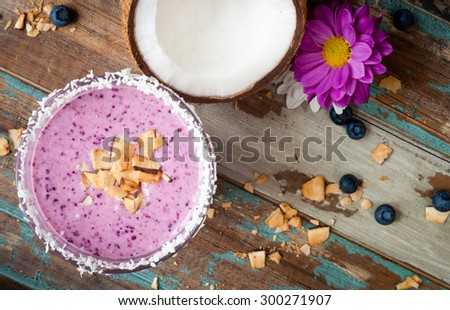 Healthy mixed berry smoothie milkshake made from blended blueberries, strawberries  with yogurt. Served in a coconut frosted glass with a stripey straw and a half coconut shell. - stock photo