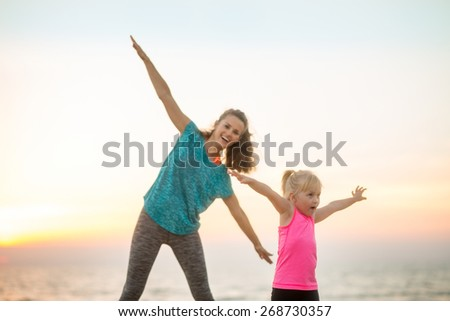 Healthy mother and baby girl having fun time on beach in the evening - stock photo