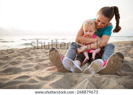 Healthy mother and baby girl hugging on beach in the evening - stock photo
