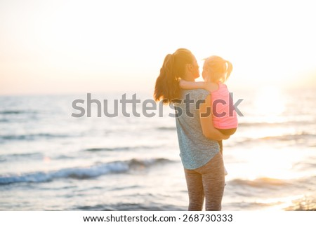 Healthy mother and baby girl looking into distance on beach in the evening. rear view - stock photo