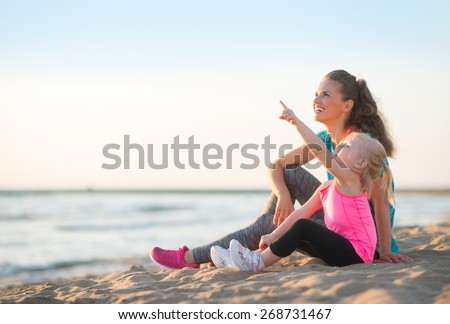 Healthy mother and baby girl pointing while sitting on beach in the evening - stock photo